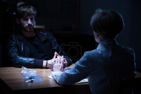 Policewoman interrogating young criminal