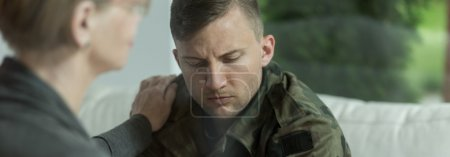 Photo for Psychologist comforting and supporting young soldier with trauma - Royalty Free Image