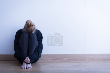 Photo for Image of a woman siiting curled up on the ground - Royalty Free Image