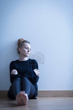 Photo for Photo of a depressed girl sitting with crossed arms - Royalty Free Image