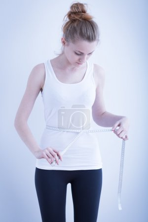 Photo for Photo of a skinny girl measuring waist - Royalty Free Image