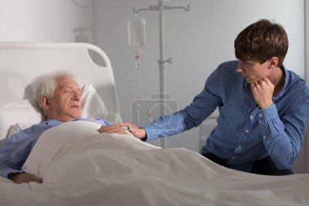 Photo pour Aîné malade dormir et un parent sa main - image libre de droit