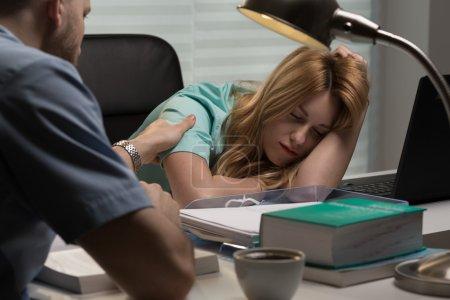Photo for Image of doctor waking up nurse sleeping on desk - Royalty Free Image