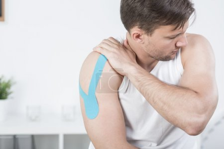Athletic man during kinesiotherapy