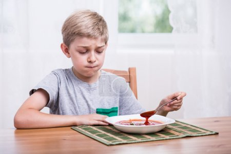 Child eating soup with disgust