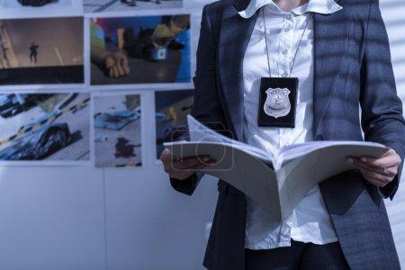 Photo pour La policière examine les dossiers et les documents - image libre de droit