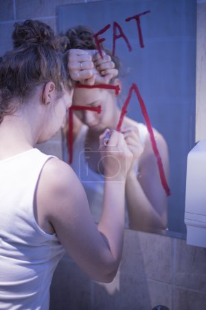 Photo for Girl with complexes is writing on mirror - Royalty Free Image