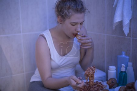 Photo for Teenage bulimic girl is eating in bathroom - Royalty Free Image