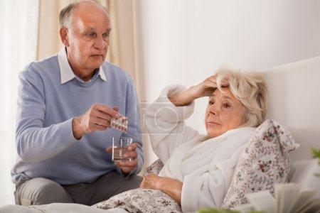 Photo pour Homme âgé donnant à sa femme malade des pilules et un verre d'eau - image libre de droit