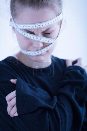 Photo pour Jeune femme anorexique enveloppée dans un ruban à mesurer - image libre de droit