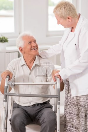 Photo for Professional carer helping her elderly patient to use a walking frame - Royalty Free Image