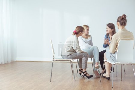 Photo for Four women talking in group about problems - Royalty Free Image