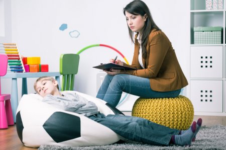 Photo for Misbehaving boy lying on sack chair during home session with psychologist - Royalty Free Image