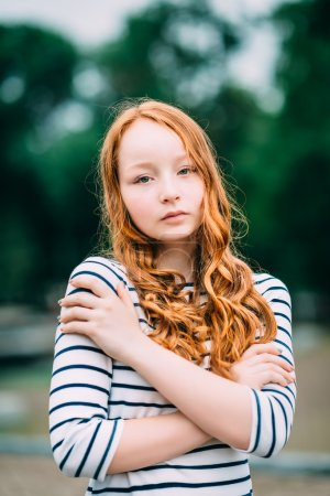 Lovely red-haired girl hugging herself and looking at camera. Beautiful young woman with red hair and green eyes in summer park. Sad teenage girl feeling herself lonely. Solitude, loneliness concept