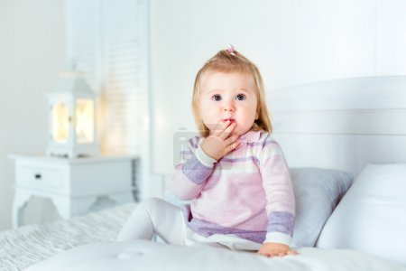Funny amazed blond little girl sitting on bed in bedroom. White interior, big bed, bedside table and night lamp. Girl touches her mouth by hand