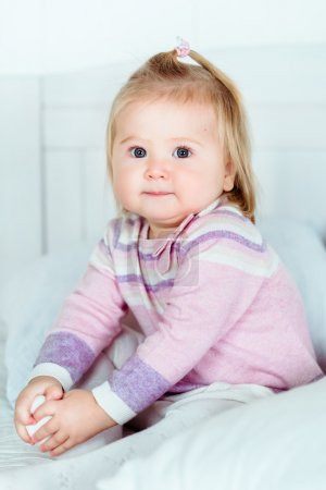 Cute blond little girl with big grey eyes and plump cheeks sitting on bed in bedroom and holding her leg with her hands