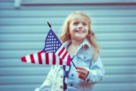 Flying american flag in little girl hand. Selective focus, blurred background. Independence Day, Flag Day concept. Vintage and retro toning. Instagram filters