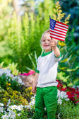 Smiling blond little boy holding american flag and waving it in sunny park or garden on summer day. Portrait of child on blurred background. Independence Day, Flag Day concept
