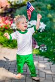 Funny laughing little boy with blond hair holding american flag and waving it in sunny park or garden on summer day. Portrait of child on blurred background. Independence Day, Flag Day concept