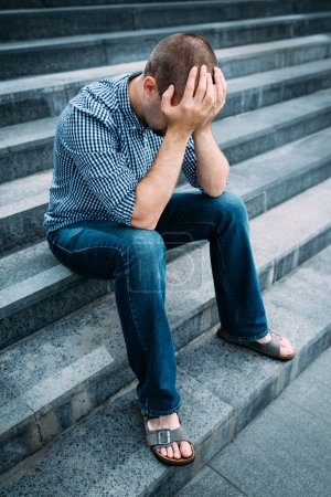 Photo for Sad young man covering his face with hands sitting on stairs of big building. Feelings of sadness, despair and tragedy - Royalty Free Image