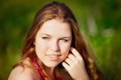 Close-up portrait of young woman with long red hair touching her face with her hand. Ginger girl sitting on grass in summer sunny field. Femininity concept