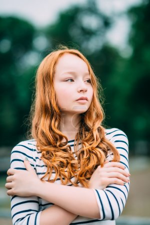 Outdoor portrait of pretty red-haired girl with green eyes who hugging herself. Adorable young redhead woman standing in summer park. Sad teenage girl with long curly red hair feeling herself lonely. Solitude, loneliness concept.