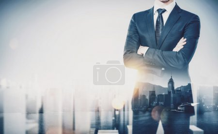Photo for Young businessman wearing modern suit and standing with his arms crossed. Double exposure. - Royalty Free Image