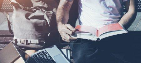 Photo pour Homme élégant portant un t-shirt blanc assis parc de la ville et le livre de lecture. Étudier à l'Université, travailler sur un nouveau projet. Livres, ordinateur portable, banc de sac à dos . - image libre de droit