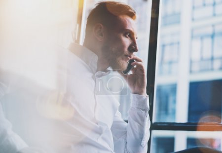 Photo for Portrait bearded adult businessman working on modern loft office. Man wearing white shirt and using contemporary smartphone. Panoramic windows background. - Royalty Free Image