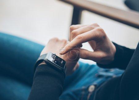 Closeup photo of female hand touching screen generic design smart watch. Film effects, blurred background. Horizontal