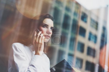Photo for Photo business woman wearing modern white shirt, talking smartphone and holding documents in hands. Open space loft office. Panoramic windows background. Horizontal mockup. - Royalty Free Image