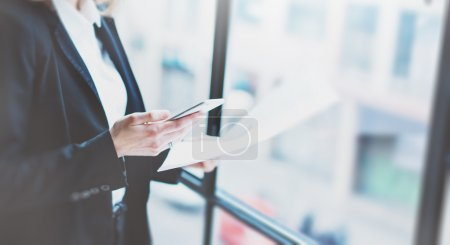 Closeup photo business woman wearing suit, looking smartphone and holding documents in hands. Open space loft office. Panoramic windows background. Wide mockup. Film effect