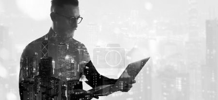Photo for Double exposure bearded businessman wearing black shirt and glasses.Banker holding contemporary notebook hands,work online banking. Modern skyscraper city background. - Royalty Free Image
