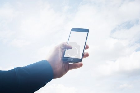 Double exposure photo businessman holding modern smartphone hand, touching empty white screen. Clouds background, ready for your business information. Horizontal mockup. Film effect
