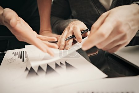 Business situation,signs reports. Photo female hand showing document. Man holding report and using pen. Working process modern office,discussion startup,finance analyze. Horizontal. Film effect