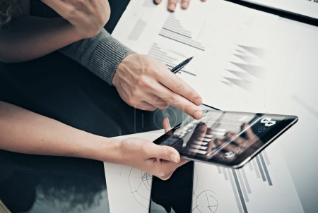Research department working process.Closeup photo woman showing business reports modern tablet. Statistics graphics screen.Banker holding pen for signs documents,discussion startup idea.Film effect