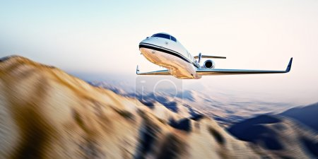 Picture of white modern and luxury generic design private jet flying in blue sky at sunrise.Uninhabited desert mountain background.Business travel picture.Horizontal,motion blurred effect.3d rendering