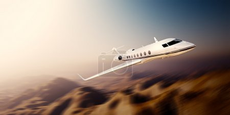 Image of white modern and luxury generic design private jet flying in blue sky over uninhabited desert.Mountains background.Business travel concept. Horizontal,motion blurred effect. 3d rendering