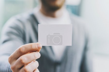 Closeup photo man wearing casual shirt and showing blank white business card. Blurred background. Ready for private information. Horizontal mockup