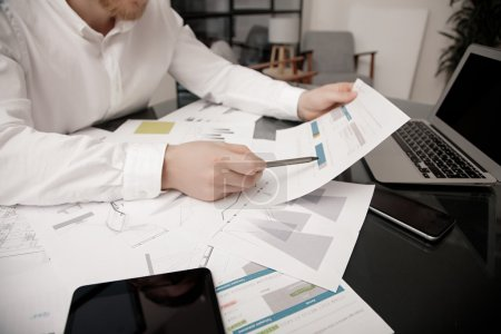 Investment manager working process.Photo bank trader work market analyze.Using electronic devices.Work worldwide stock exchanges report documents.Business project startup.Horizontal,film effect