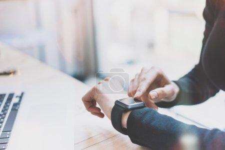 Photo Woman Working Modern loft,Using Generic Design Smart Watch.Female Hands Touching Screen Smartwatch.Account Manager Work Process. Horizontal. Burred background. Film effects