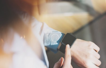 Photo for Photo Woman Relaxing Modern Loft Studio and Using Generic Design Smart Watch.Female Hands Touching Screen Smartwatch.Manage Free Time Process. Horizontal mockup. Burred background. Film effects. - Royalty Free Image