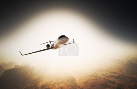 Photo White Glossy Luxury Generic Design Private Jet Flying in Sky under Earth Surface.Grand Canyon Background Sunrise. Business Travel Picture.Horizontal,Right Angle View.Film Effect. 3D rendering.