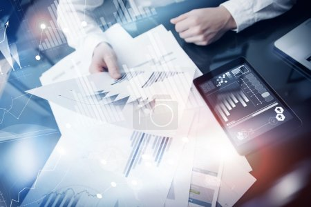 Investment manager working process.Concept photo trader work market report modern tablet.Using electronic device.Graphic icons,stock exchange reports screen interfaces.Business startup.Film effect