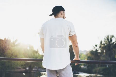Photo Bearded Muscular Man Wearing White Blank t-shirt, snapback cap and shorts in summer time. Green City Garden Park Sunset Background. Back view. Horizontal Mockup