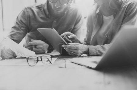Coworking process. Photo young business crew working with new startup project.Notebook on wood table.Woman showing reports digital tablet,man holding document.Blurred background,black white.Horizont.