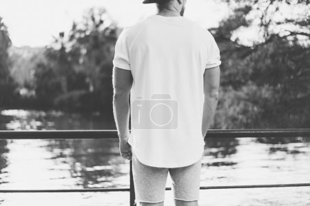 Photo Bearded Muscular Man Wearing Blank t-shirt, snapback cap and shorts in summer time. Relaxing  near the lake. Green City Garden Park Sunset Background.Back view. Black White Mockup