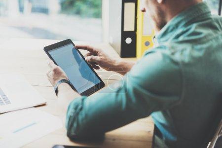Social Trading Online Markets analyze reports.Man working wood table Modern Interior Design Loft Place.Businessman Work Coworking Studio.Using Digital Tablet Hands.Blurred Background.Business Startup.