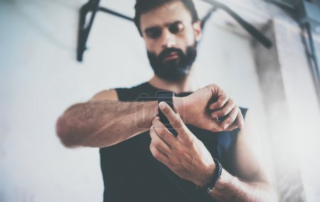 Close-up Shot Young Bearded Sportive Man After Workout Session Checks Fitness Results Smart Watch.Adult Guy Wears Sport Tracker Wristband Arm.Training hard gym.Horizontal bar background.Blurred.
