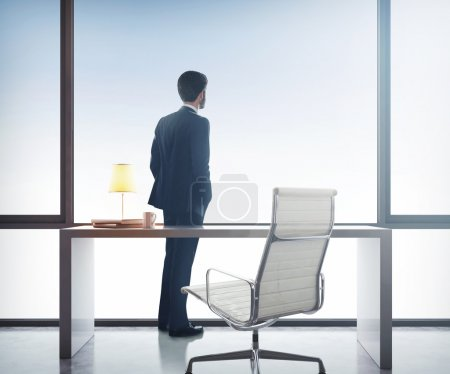 Photo for Businessman standing in office and looking through window - Royalty Free Image